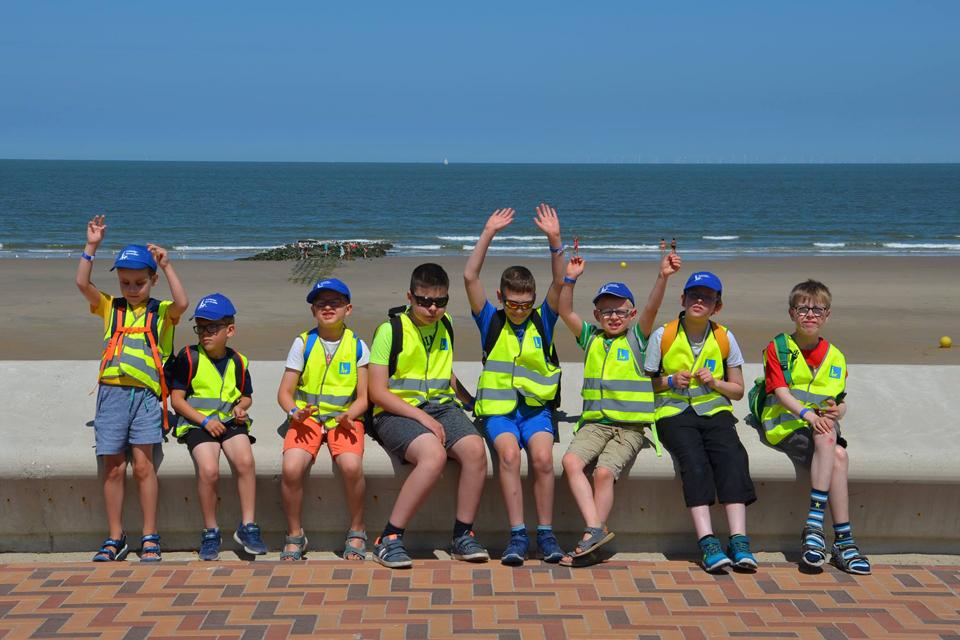 Groep kinderen met op de achtergrond de zee.