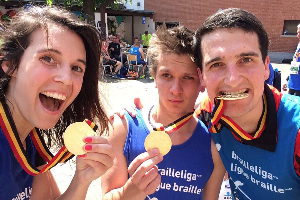 Des coureurs de la Ligue Braille montrent leur médaille.