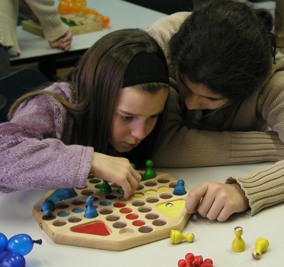 Een meisje met een visuele handicap speelt een spel dat door de Brailleliga werd aangepast.